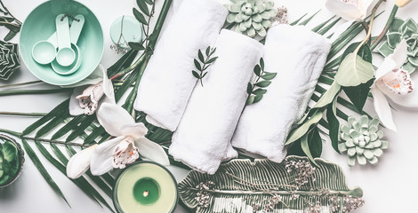Spa treatment setting with towels, green candle, tropical leaves, white orchid flowers, top view. Wellness concept