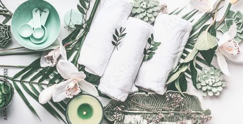 Ustawienie leczenia uzdrowiskowego z ręczniki, zielona świeca, liści tropikalnych, białe kwiaty orchidei, widok z góry. Koncepcja odnowy biologicznej