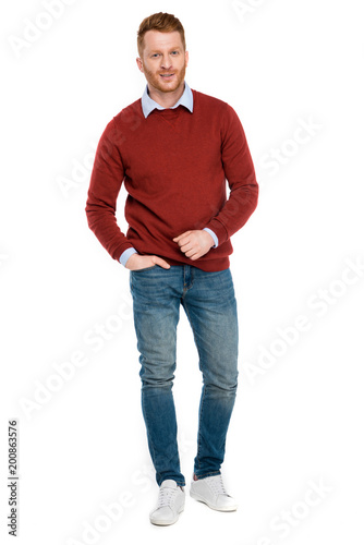 full length view of handsome redhead man looking at camera isolated on white