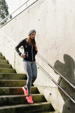 Sporty urban woman running downstairs. Female athlete trainning and exercising in city stairs. - 200868565