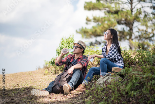 Foto Murales Thoughtful hiking couple looking away while relaxing in forest