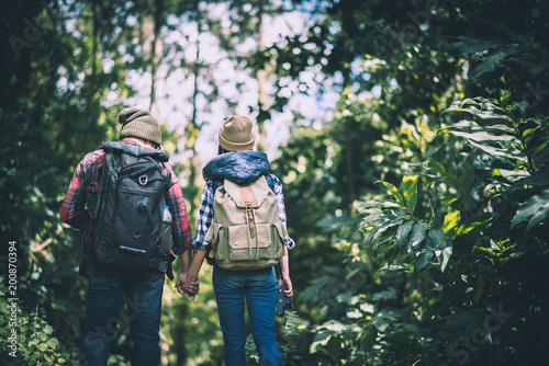 Young couple walking with backpacks in forest. Adventure hiking, Enjoy holidays together,