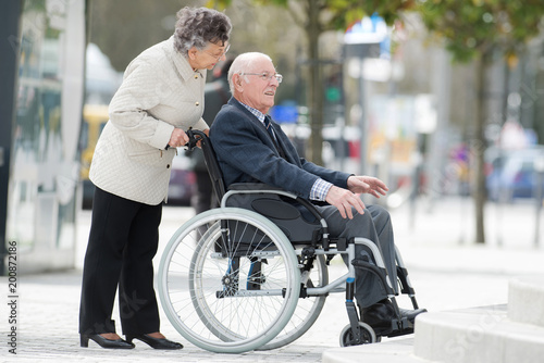Foto Murales senior couple in wheelchair enjoying a day in the city