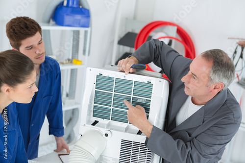 young apprentices repairing air conditioner at class