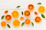 Fresh orange slices and leaves on a white wooden background