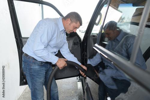 człowiek odkurzający lub czyszczący samochód
