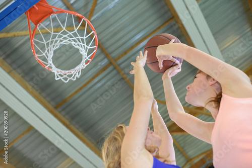 Fotobehang Basketbal Women plaing basketball, aiming for hoop