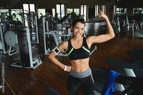 A beautiful young woman (girl) smiles at the camera while she is training at the gym. Concept: Sport, love for sport, fitness. - 200896513