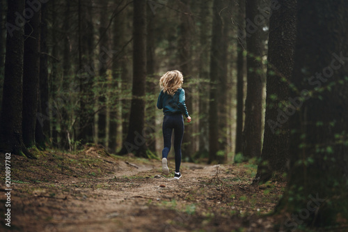 Young fitness woman running in the forest trail