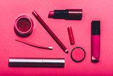 Beauty tools laying on a vivid pink background.