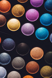 Colorful eyeshadows in rows on black background.
