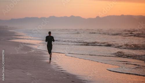 Foto Murales Runner training on the beach in morning