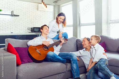 Happy family with guitar singing songs sitting in the room.