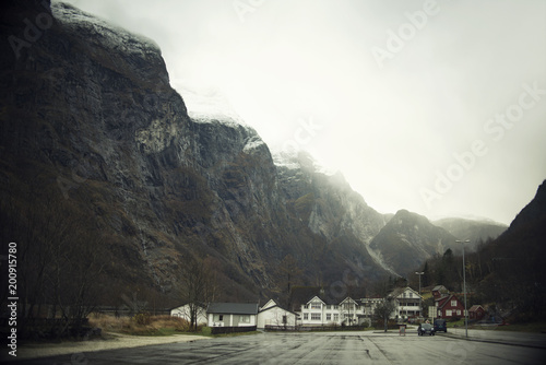 Foto Murales Paisaje montañoso un día nublado y gris con un pequeño poblado en la falda de la montaña