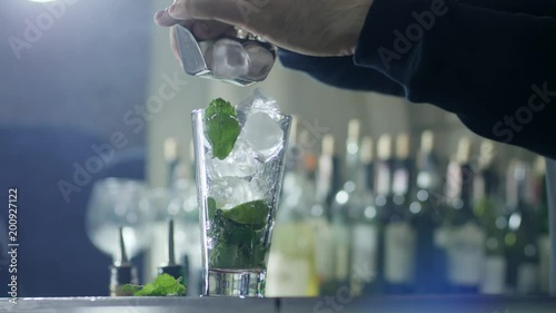hand of barkeeper add ice cubes in transparent glass with mint and lime on table in easy haze close-up on unfocused background