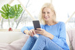 Relaxed woman relaxing at home and using cell phone and making a call