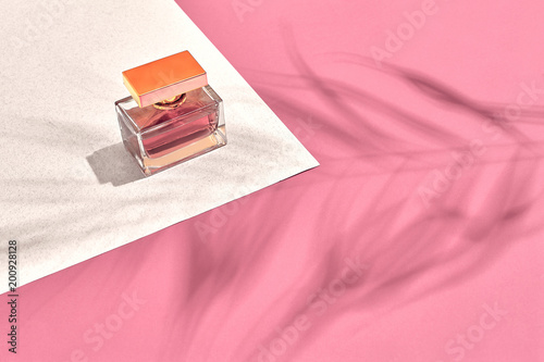 Fashionable Women's Cosmetics and Accessories. Flat Lay. Perfume. Pink and white background. Shadow from a palm leaf - 200928128