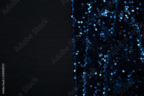 dark background of black fabric and blue shiny pieces - 200928751