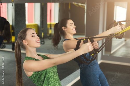 Women performing TRX suspension training in gym