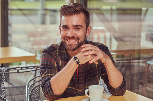 A handsome fashionable male with stylish haircut and beard, wearing fleece shirt, drinking coffee at the cafeteria. © Fxquadro