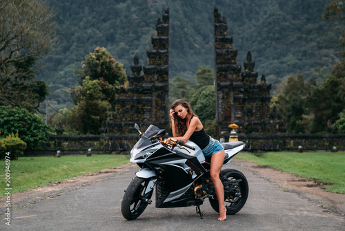 gorgeous sexy girl sits on a motorcycle in black and white. A model dressed in a black jersey and denim shorts posing on a bike. woman Motobike drivers.