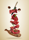 Flying pieces of raw beef steaks from cutting board - 200947393