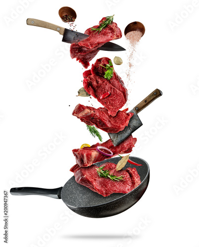 Flying pieces of beef steaks from pan on white background