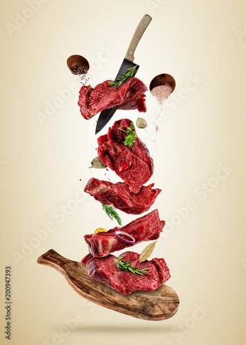 Flying pieces of raw beef steaks from cutting board