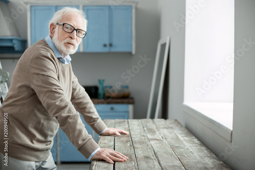 Old age. Nice elderly man looking at you while standing in the kitchen at home