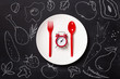 Top view on plastic forks and clock on white plate at black background - 200952304