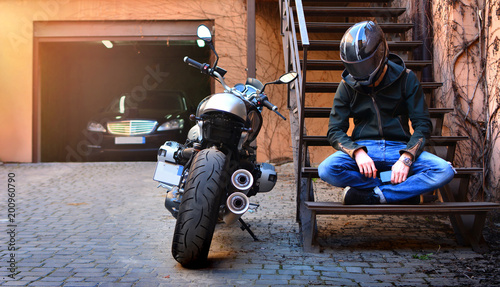Lonely biker thought about and rested on the stairs near the motorcycle. Motorbike and motorcyclist in a helmet on a city street.