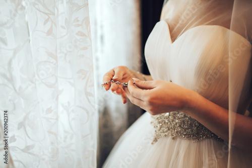 Pretty bride dressing up before wedding ceremony