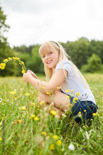 Foto Murales Blondes Mädchen pflückt Löwenzahn Blumen