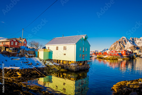 Outdoor view of a wooden building in a lake shore in a port in Henningsvaer on Lofoten islands
