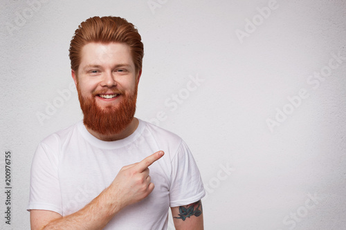 Kryty strzał młodych podekscytowany zaskoczony rude facet z brodą punkt z palcem na bok, uśmiecha się i czuje się szczęśliwy