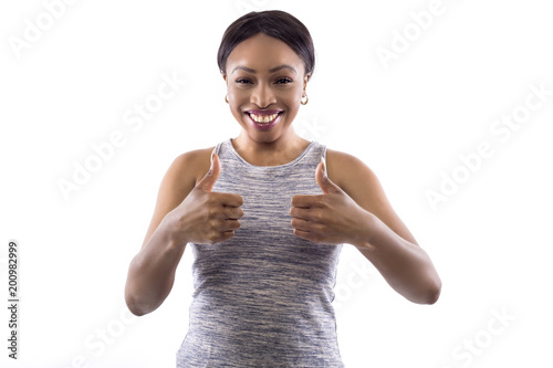 Black female wearing athletic outfit on a white background as a fitness trainer with thumbs up