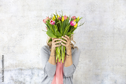 Young pretty woman with a bouquet of flowers stands in front of concrete wall and is happy about mother's day, birthday, wedding day - 200992964