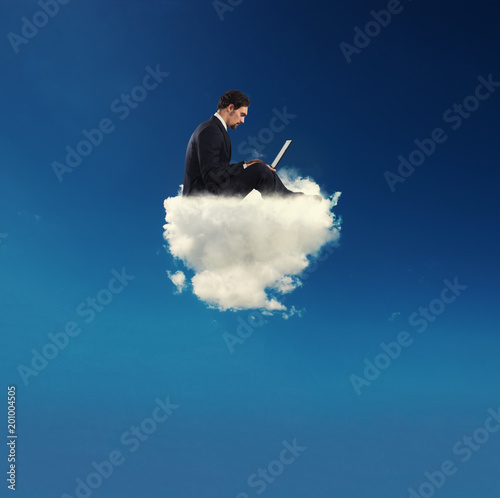 Fototapeta Businessman connected with his laptop over a cloud. concept of social network and internet addiction
