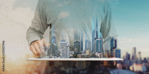 Foto Murales a man using digital tablet, and modern buildings hologram. Real estate business and building technology concept