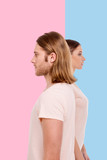 Diverging perspectives. Handsome bristled man and his girlfriend standing shoulder-to-shoulder but looking into different directions while posing against pink and blue backgrounds - 201008199