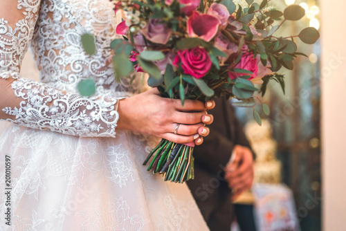 Bride's hand with wedding ring and bouquet of flowers