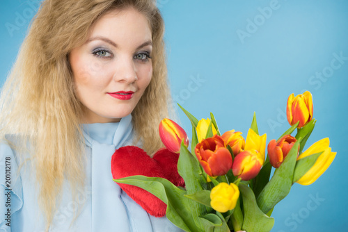 Woman holds tulips and red heart