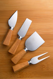 Cheese cutter set with wooden handles. Group of cheese knives on a wooden background. Top view