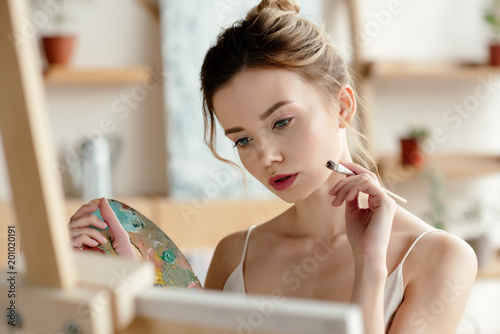 attractive girl with brush and palette painting picture in art studio