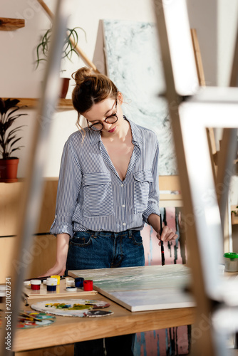 Foto Murales young stylish female artist in eyeglasses painting
