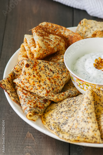 Delicious poppy seed crepes (blinis) and sour cream sauce with dill served on a white plate on a wooden background.