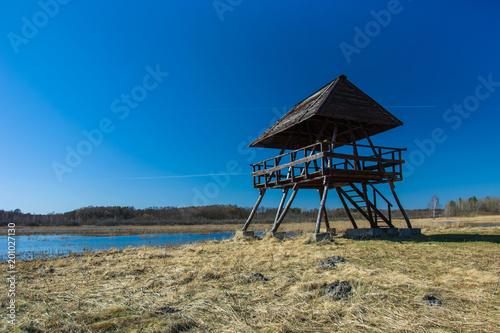 Fotobehang Blauwe jeans Wooden lookout tower and wild meadow