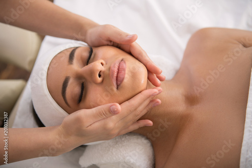 Facial procedure. Attractive nice woman lying with her eyes closed while enjoying facial massage - 201032387