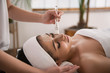 Spa treatment. Nice attractive pleasant woman feeling relaxed while having a facial mask applied on her face