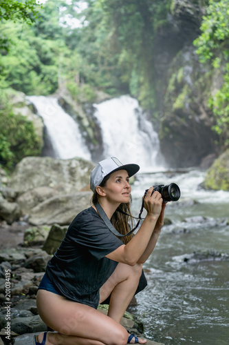 side view of woman in cap with photo camera in hands and Aling-Aling Waterfall on backdrop, Bali, Indonesia - 201034135